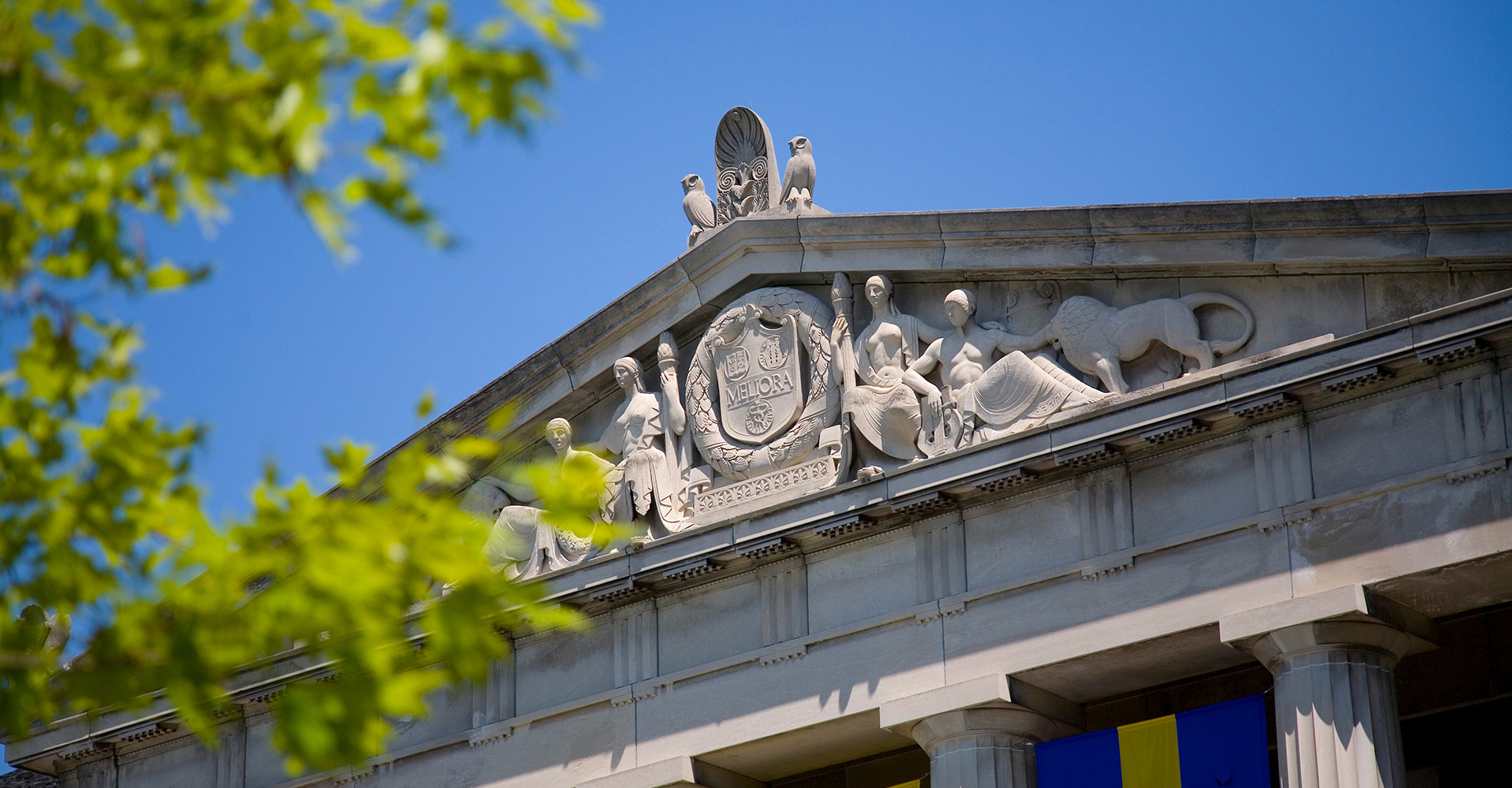 frieze of rush rhees library with foreground tree branches