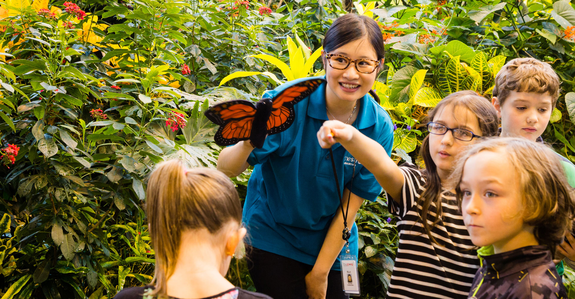 Female teacher with students holding a butterfly