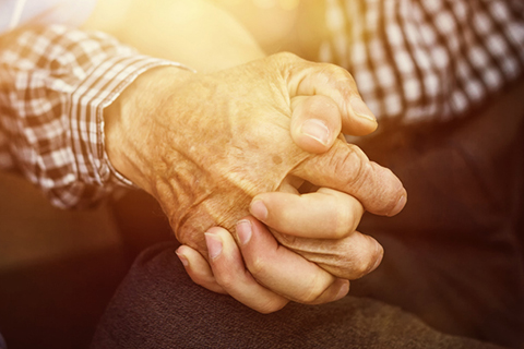 elderly hand holding a younger one