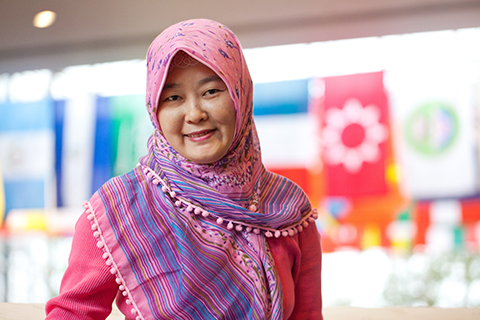 student in pink headscarf in Wilson Commons with international flags in background