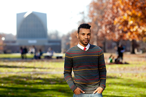 student poses on quad with chapel in background
