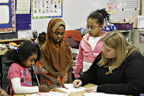 teacher working with diverse young students