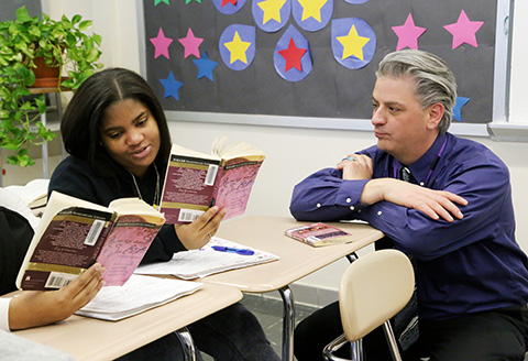 teacher working with two high school students reading Romeo and Juliet