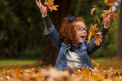 young girl playing in pile of leaves