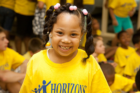 young smiling girl in Horizons at Warner t-shirt