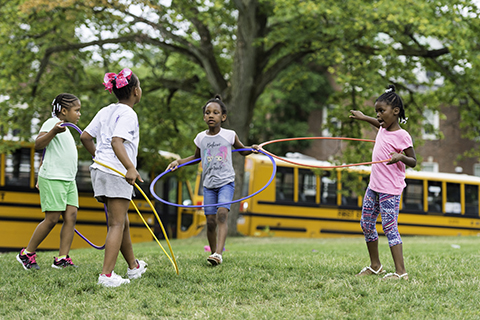 kids playing with hula hops at recess with busses in background