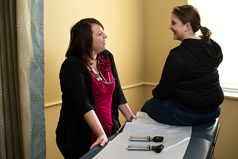 patient and health care provider converse in exam room