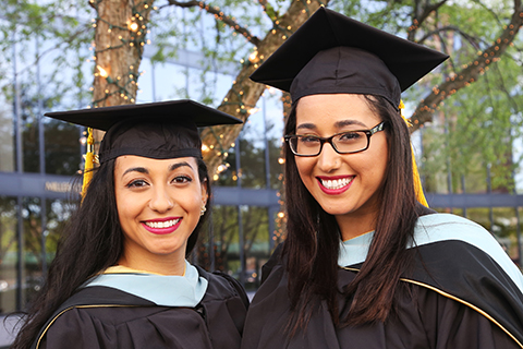 Sisters graduate, in caps and gowns
