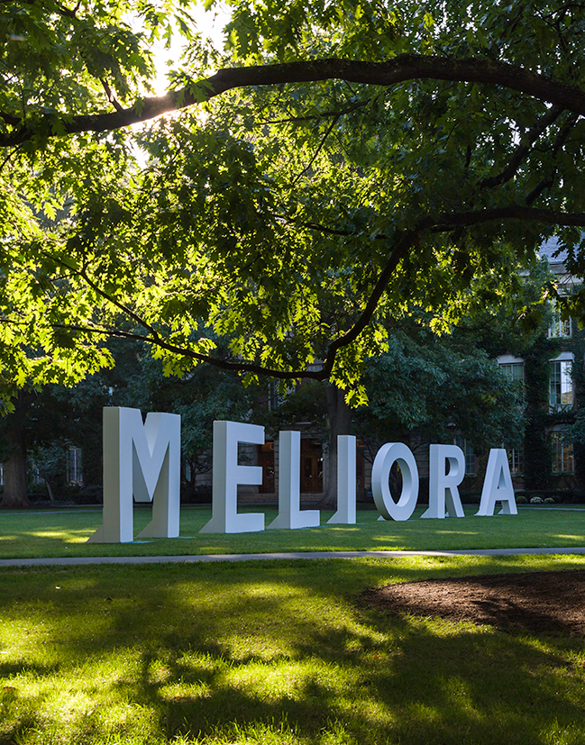 large letters that spell out MELIORA are on the eastman quad