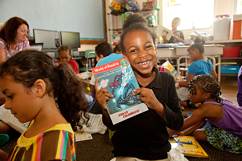 elementary student in classroom showing off new book