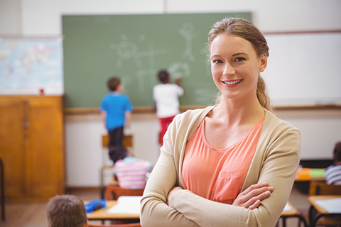 smiling teacher with arms crossed and classroom with students behind her