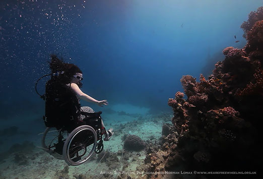 Image of a woman scuba diving in a wheelchair next to a coral reef