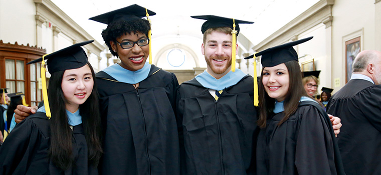 four graduate students in caps and gowns