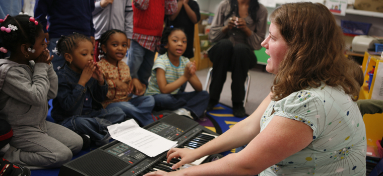 teacher playing piano for young students