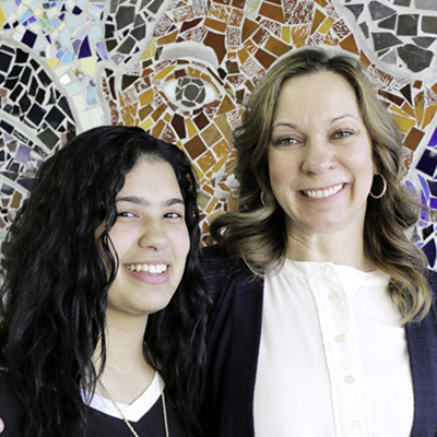 student and teacher in front of mosaic