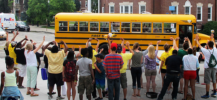 students waving to a busload of children