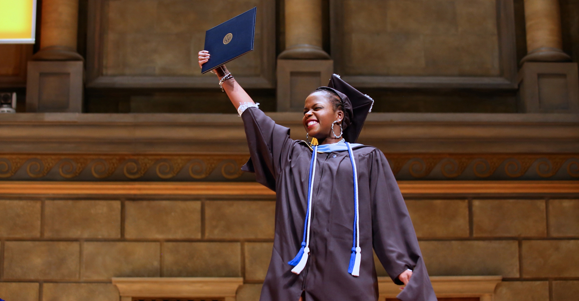 A graduate holds up her diploma with joy